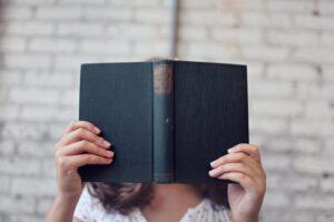 student hidden behind a book
